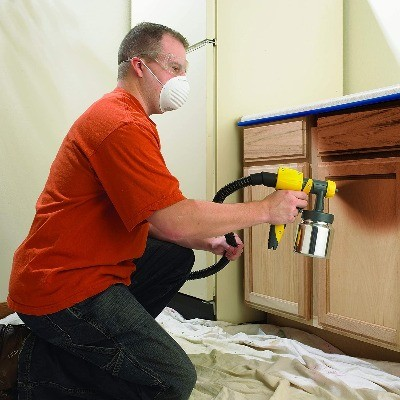 image of a woodworker using the best hvlp spray gun for wood finishing
