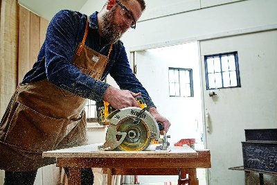 Image of a woodworker using DEWALT, the best cordless circular saw for beginners