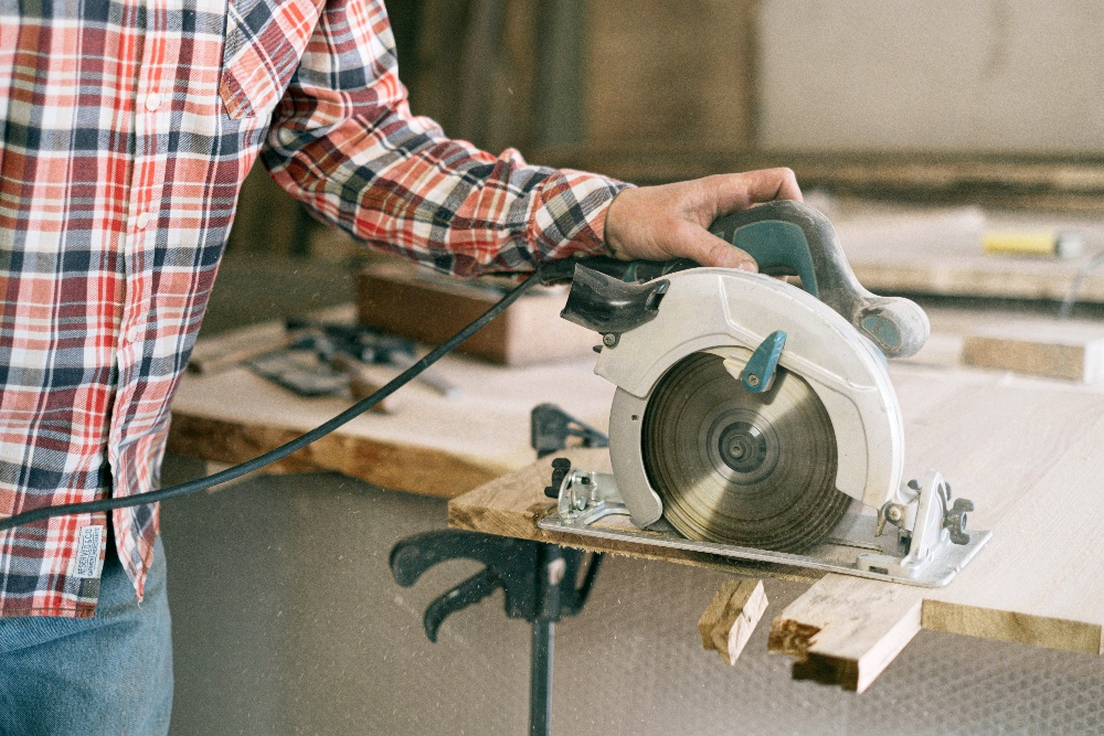 Image of a woodworker using a miter saw, one of the many different types of woodworking saws